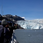 Two visitors take pictures of a tidewater glacier from the deck of a tour boat.