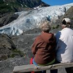 A couple sits on a park bench, viewing the nearby Exit Glacier.
