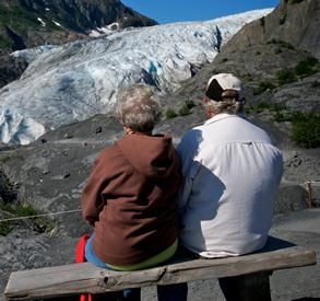 A couple sit on a bench located on the trail to the edge of Exit Glacier, and look to the glacier off in the distance.