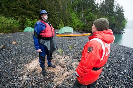 A park ranger speaks with a kayaker in front of his campsite.