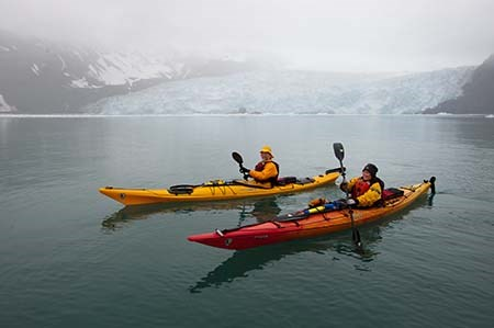 Two kayakers sit in the water in front of a large tidewater glacier.