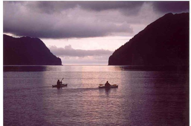 Two kayakers float in the ocean, framed by steep shorelines.
