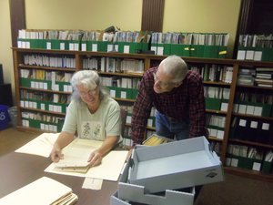 Two volunteers look through documents inside the History Center.