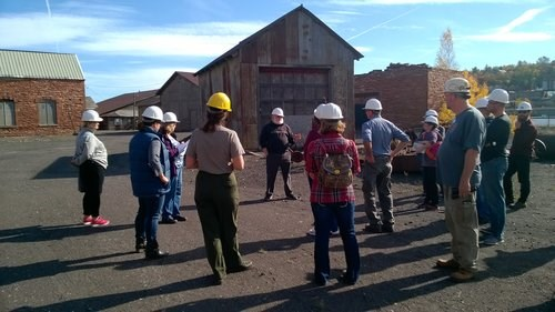 People with hardhats on listen to a speaker at an outdoor industrial site.
