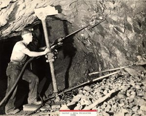 A miner operates a pneumatic drill to make blasting holes underground.