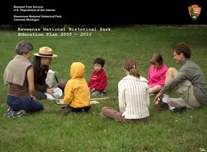 A ranger interacts with young children and their caregivers sitting outside on grass.