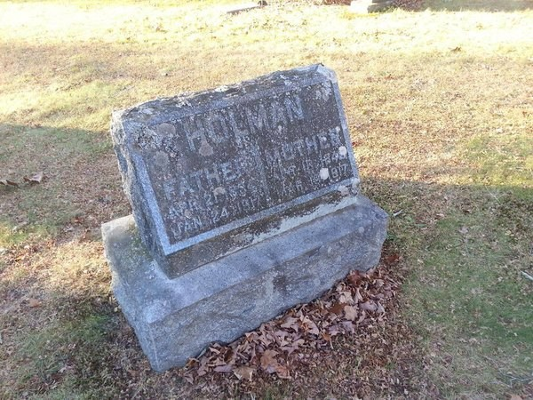 A grave marker in a cemetery that has weathered much of the text.
