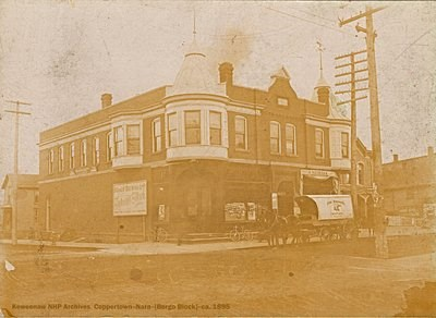 A building is situated on a corner of two streets with a horse-drawn wagon out front.
