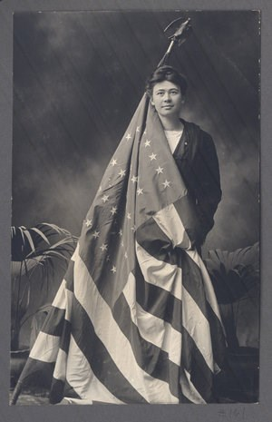 A woman poses for a photo holding an American flag that is partially draped around her body.