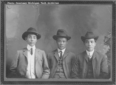 Three men with hats on sit down and pose for a photograph.