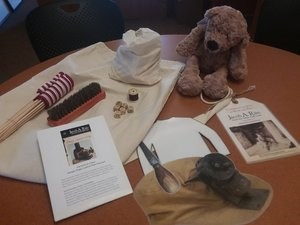 A teddy bear, magic lantern slide, dice, spool of thread, and other items are displayed on top of a canvas bag.
