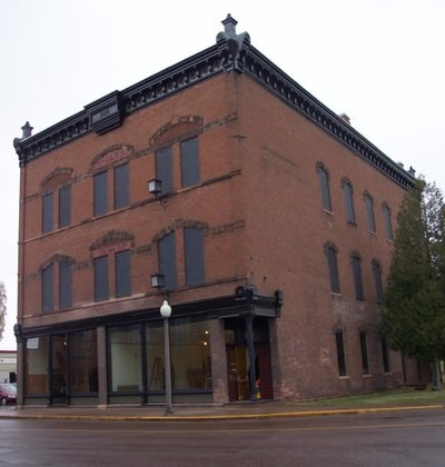 The exterior of a three story brick building with large windows on the first floor.