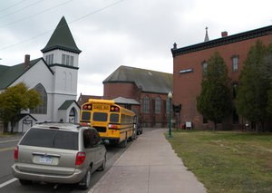 A school bus is parked on the street outside of the Calumet Visitor Center building.