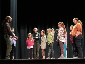 A group of students listen to directions from an adult on a stage.