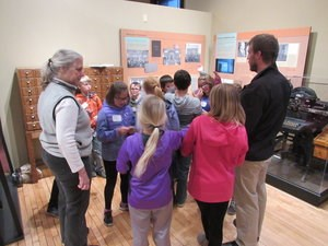 A group of students look at a museum exhibit with adults.