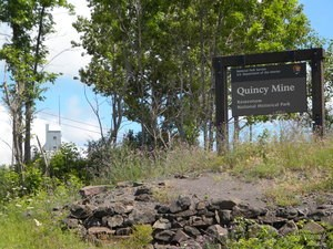 The Quincy Unit park sign is in the right foreground, with the top of the No. 2 shaft-rock house in the left background.