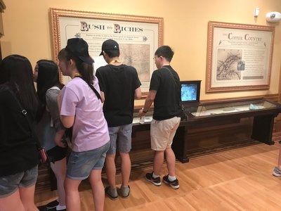 A group of students examine exhibits in a museum.