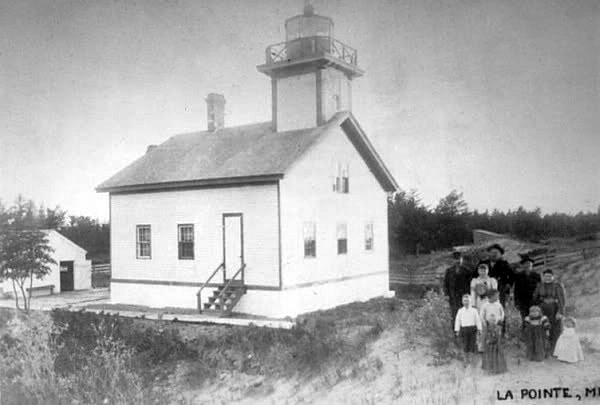 Old LaPointe Lighthouse with a group of people standing in front of it.