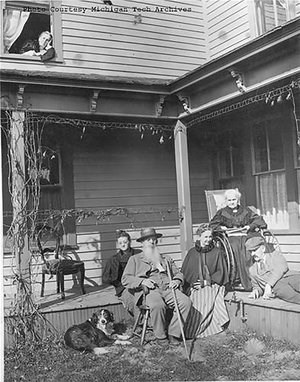 Five people and a dog sitting outside on the front porch of a house.