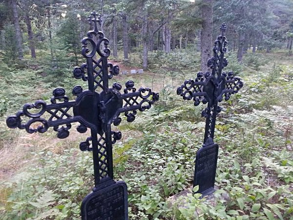 Two cross grave markers are surrounded by a small fence.
