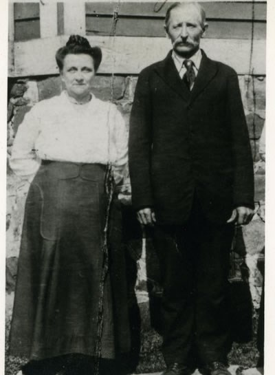 A man and woman pose for a photograph while standing in front of a building.