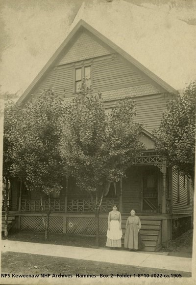 Two women with aprons stand in front of a house with trees.