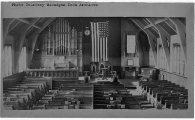 The interior of a church with lines of pews and an American flag hung up at the front.