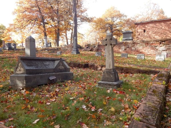Grave markers are surrounded by a small, masonry fence in a cemetery.