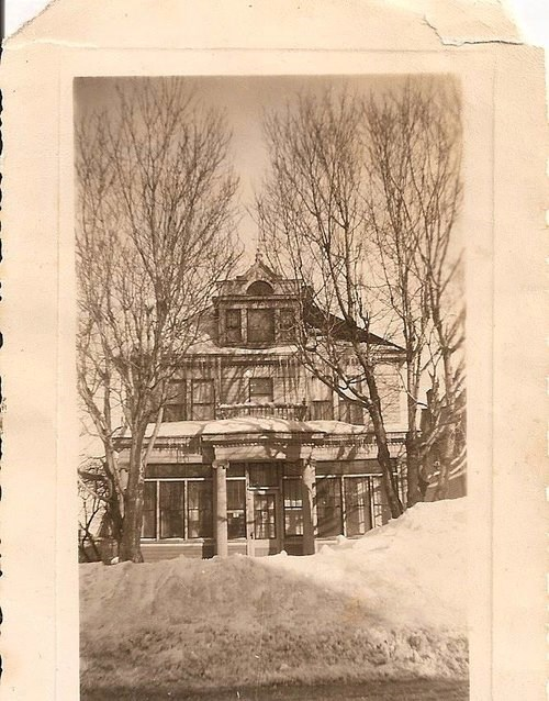 The front of a two-story house with snow in front of it.