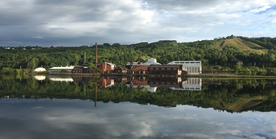The Quincy Smelter from across the Portage Canal with cloudy skies and glassy water