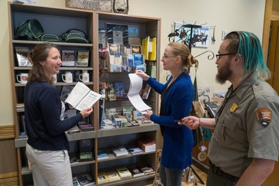 Two people look at books and ask questions of a park ranger.