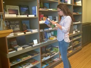A person reads a book in a store.