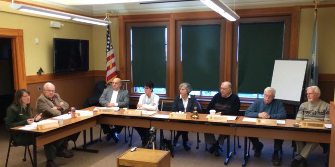 Advisory Commission members sit around a table and discuss topics at a quarterly meeting.