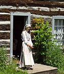 A costumed interpreter at Old Victoria awaits visitors before giving a guided tour of the cabins.