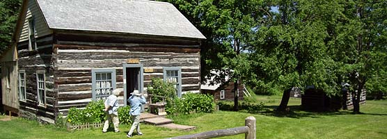 Visitors stroll by a former miner's cabin at old Victoria.