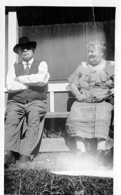 A man and woman sit on a porch situated on the front of a house.