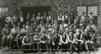 A large group of men pose for a photograph outside of a masonry structure.