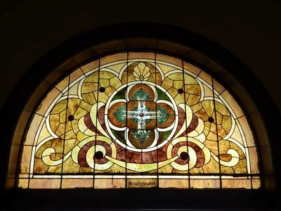 "A stained glass window in a church is labeled with the name ""Michael Schmalzel."""