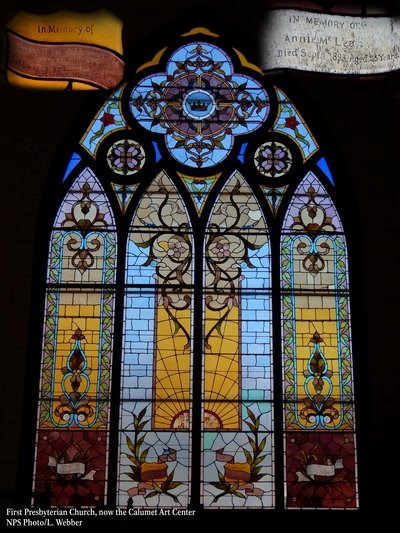 A large stained glass window is multi-colored with different flower and plant depictions.