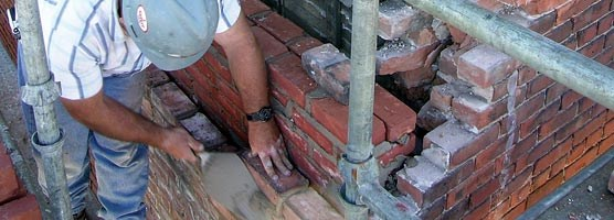 A mason repairs brickwork on the Union Building in Calumet.