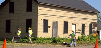 Members of the park Youth Conservation Corps clean around the outside of a Quincy company house.