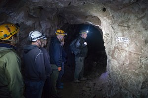 A group of people with hardhats and head lamps explore a former underground copper mine with a tour guide.