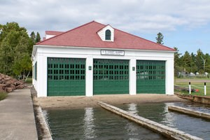 Exterior building with white siding and large green doors that is part o the Eagle Harbor Lifesaving Station complex.