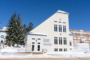 Blue and white exterior of the Finnish American Heritage Center in winter.