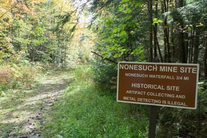 "A brown sign with white lettering next to a trail reading ""Nonesuch Mine Site."""