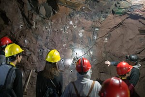 A group of visitors with hardhats explores the underground of the Quincy.