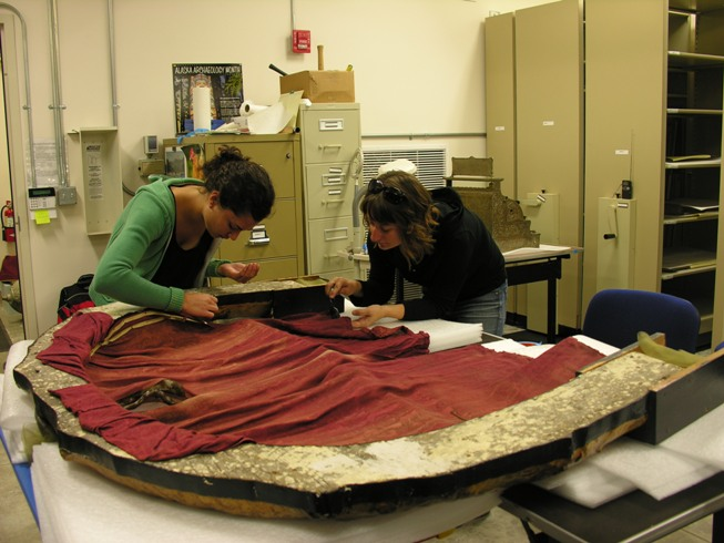 Nicole and Katie working together to surface clean a textile