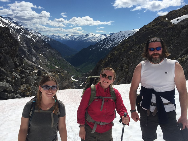 Three people stand on a mountain snow patch