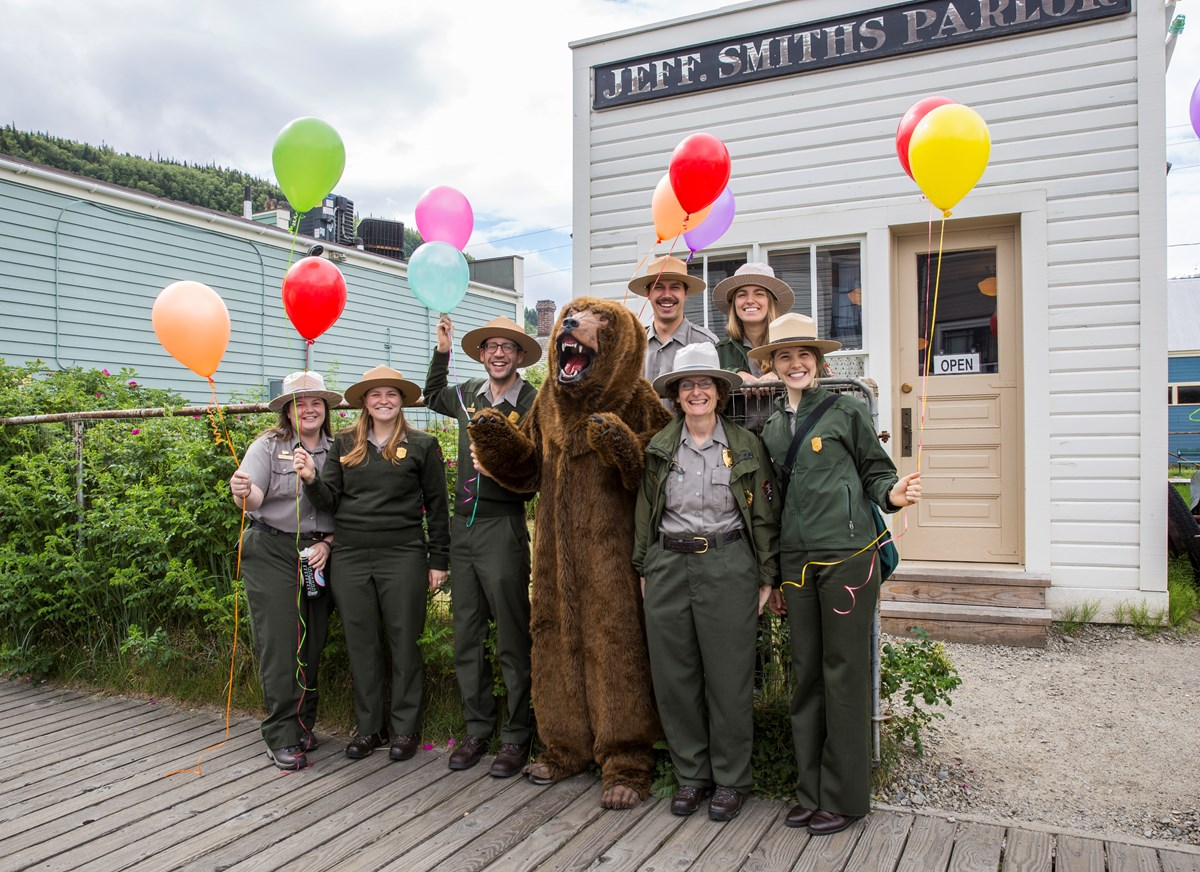A group of rangers with balloons and a bear costume pose in front of the Jeff. Smiths Parlor.
