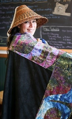A woman in woven hat and a colorful blanket